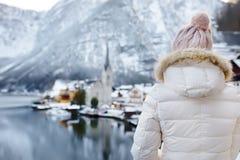 Kvinnan tycker om scenisk sikt för vinter av byn av Hallstatt i de österrikiska fjällängarna royaltyfri bild