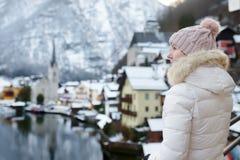 Kvinnan tycker om scenisk sikt för vinter av byn av Hallstatt i de österrikiska fjällängarna arkivfoto