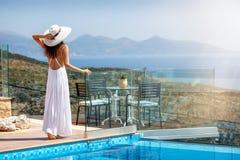 Kvinnan tycker om sikten till havet vid poolsiden fotografering för bildbyråer