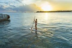 Kvinnan tycker om står upp skoveln som surfar i Key West Royaltyfri Foto
