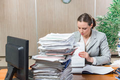Kvinnan under spänning från överdriven skrivbordsarbete Arkivfoto