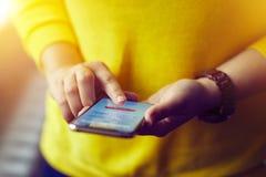Kvinnan undertecknar upp till att packa ihop med hennes mobiltelefon Royaltyfri Foto
