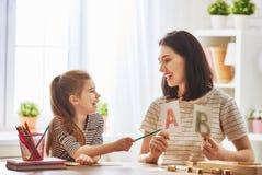 Kvinnan undervisar barnet alfabetet royaltyfri fotografi