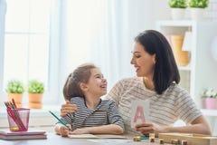 Kvinnan undervisar barnet alfabetet arkivfoton
