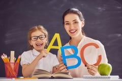 Kvinnan undervisar barnet alfabetet fotografering för bildbyråer
