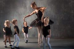 Kvinnan undervisar flickor att dansa balett Royaltyfria Foton