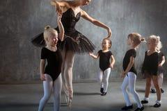 Kvinnan undervisar flickor att dansa balett Arkivbilder