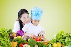 Kvinnan undervisar hennes barn att klippa grönsaker Arkivfoto