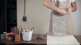Kvinnan unpackaging lera för att modellera i arbetande studio, lager videofilmer