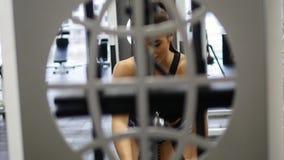 Kvinnan utbildar armar och skuldror på simulatorn i idrottshall lager videofilmer