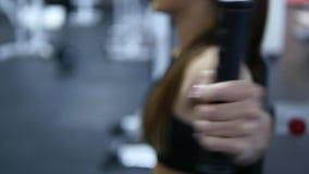 Kvinnan utbildar armar och skuldror på simulatorn i idrottshall Selektivt fokusera lager videofilmer