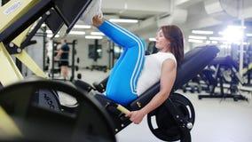 Kvinnan utbildar henne ben i idrottshallen stock video