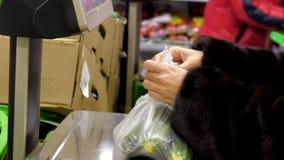 Kvinnan väger grönsaker på automatisk våg i supermarket lager videofilmer