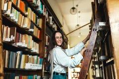 Kvinnan väljer böcker arkivfoton