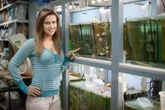 Kvinnan väljer fisken i akvarier Arkivfoto