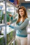 Kvinnan väljer fisken i behållare Arkivfoton