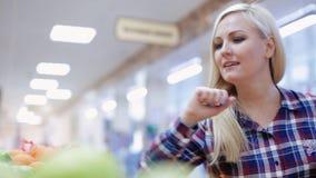 Kvinnan väljer frukt i en supermarket arkivfilmer