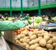 Kvinnan väljer i marknadslökarna Försäljningar av nya och organiska frukter och grönsaker på den gröna marknaden eller bönder mar arkivfoton