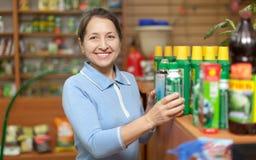 Kvinnan väljer jordbruks- kemikalieer på shoppar för trädgårdsmästare royaltyfria bilder
