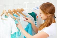 Kvinnan väljer kläder i hennes garderob Royaltyfria Bilder