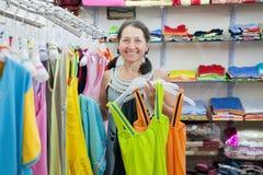 Kvinnan väljer kläder på shoppar Royaltyfria Foton