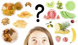 Kvinnan väljer mellan snabbmat eller sunda frukter Arkivfoto