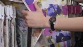 Kvinnan väljer rester av det kulöra silkespappret shoppar in stock video