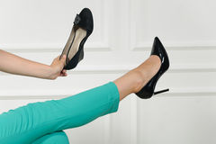 Kvinnan väljer skor med ett ben upp Royaltyfri Fotografi