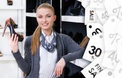 Kvinnan väljer stilfulla pumpar på försäljning Arkivfoton
