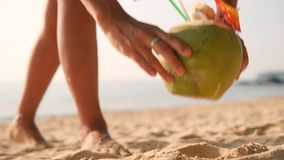Kvinnan väljer upp den läckra nya thailändska kokosnötcoctailen från sand, når han har simmat på den tropiska stranden och går bo stock video