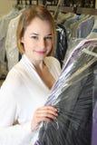 Kvinnan väljer upp kläder i en kemtvätt royaltyfria bilder