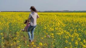 Kvinnan vänder behandla som ett barn Mamma och dotter i natur Lycklig familj i gula blommor Raps Canola, Biodieselskörd lager videofilmer