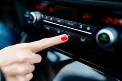Kvinnan vänder på luft som betingar i bilen Royaltyfria Bilder