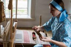 Kvinnan väver den färgrika bomullsämbetsdräkten eller klänningen, genom att använda trävävstolen i den lokala byn i Ryssland Royaltyfri Bild