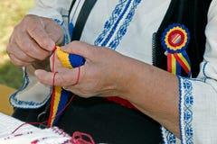 Kvinnan väver samman vid det rumänska traditionella bältet för handen Royaltyfri Fotografi