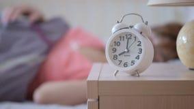Kvinnan vaknar upp och får ut ur säng arkivfilmer