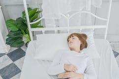 Kvinnan vilade på sängen i hennes sovrum i morgonen royaltyfri foto