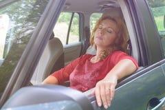 Kvinnan vilar i bilen Arkivbild
