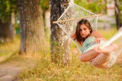 Kvinnan vilar i hängmatta Arkivbild