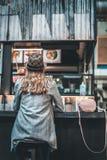 Kvinnan vilar i kafé med koppen kaffe fotografering för bildbyråer