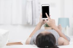 Kvinnan vilar och koppla av på säng genom att använda mobiltelefonapparater royaltyfria bilder