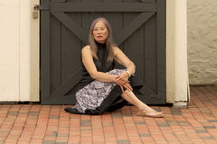 Kvinnan vilar vid den låsta dörren arkivbild