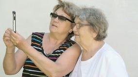 Kvinnan visar fotoet till den gamla kvinnan som använder en smartphone stock video
