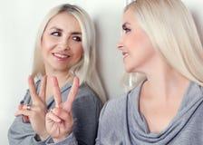 Kvinnan visar hans reflexion nummer 2 på fingrarna som står i spegeln Royaltyfri Foto
