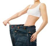 Kvinnan visar henne att väga förlust genom att ha på sig gammal jeans Royaltyfria Foton