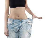 Kvinnan visar henne att väga förlust genom att ha på sig gammal jeans Royaltyfri Fotografi