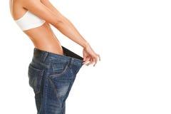 Kvinnan visar henne att väga förlust genom att ha på sig gammal jeans som isoleras på Royaltyfri Bild