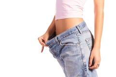 Kvinnan visar henne att väga förlust genom att ha på sig gammal jeans som isoleras på vitbakgrund Royaltyfri Bild