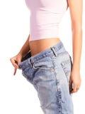 Kvinnan visar henne att väga förlust genom att ha på sig gammal jeans som isoleras på vitbakgrund Royaltyfri Foto