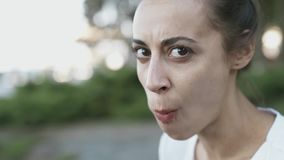 Kvinnan visar jokingly hur hon biter ivrigt av ett stycke av dillanden och äter med en rolig framsida lager videofilmer